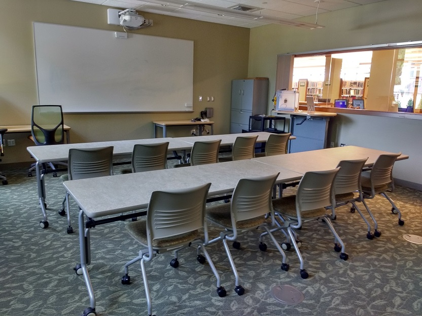 a classroom with white board/projector screen and ten chairs at two rows of desks