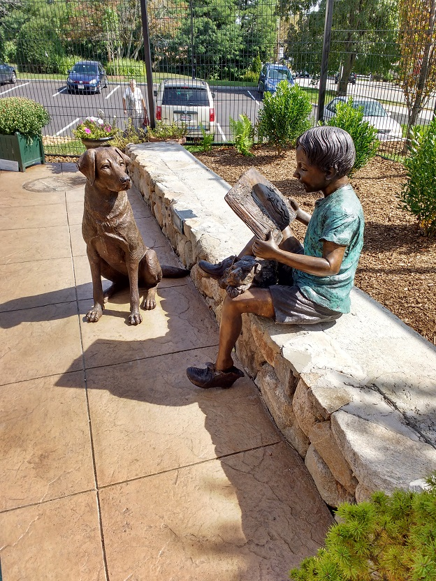 painted brass sculpture of a boy reading a book to a dog