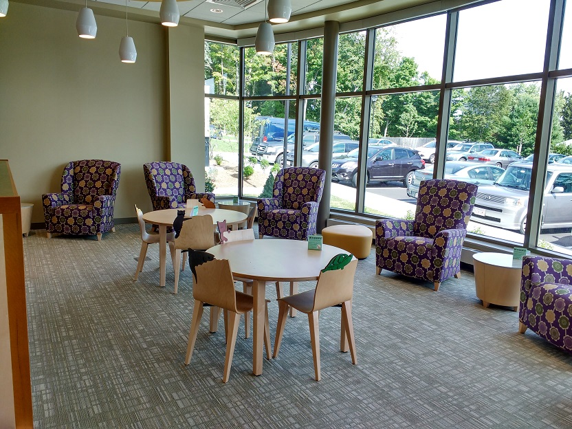 easily movable tables and chairs set up around a huge window overlooking the parking lot