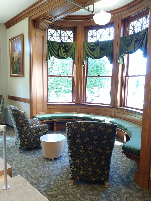corner windows with ledge seating, chairs, and a side table